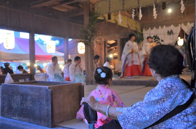 A senior and a village child watch the Maiko-mai dance